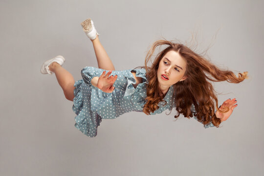 Beautiful girl levitating in mid-air, falling down and her hair messed up soaring from wind, model flying hovering with dreamy peaceful expression. indoor studio shot isolated on gray background
