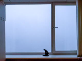 A plastic window, behind which only white fog is visible. There is a black steppler on the window sill.