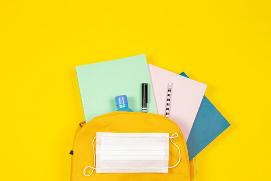 Education, learning, back to school during pandemic. Top view to open backpack with notebooks, school supplies, hand sanitizer and protective medical face mask on yellow background