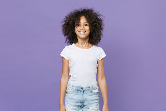 Smiling little african american kid girl 12-13 years old in white t-shirt isolated on pastel violet wall background studio portrait. Childhood lifestyle concept. Mock up copy space. Looking aside.