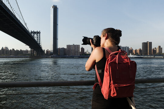 Adult woman tourist taking pictures of Brooklyn Bridge.