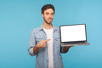 Portrait of happy smiling handsome man in worker denim shirt pointing at laptop screen with empty display, mock up free space for commercial image or text. studio shot isolated on blue background