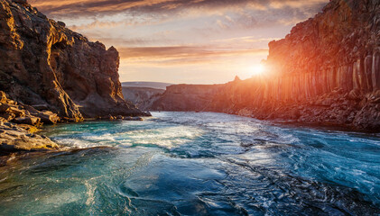 Scenic Image of nature of Iceland during sunset. Tipical icelandic landscape of summer. Majestic basalt canyon, powerful river and colorful sky. Iceland Best country for travel locations.