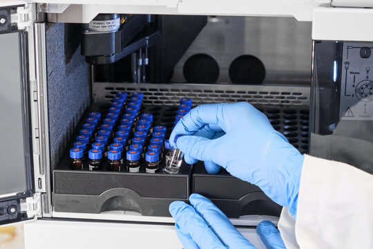 Close up woman hand in a rubber gloves put sample in a glass vial with blue cap into the autosampler rack in HPLC system. High performance liquid chromatography for separation compounds . Scientific