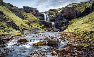Amazing Icelandic landscape with Powerful waterfall in basalt canyon with green grass and tipical lava moss. Travel adventure and freedom concept.  Famous travel locations. Creative artistic Image.