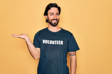 Obraz Young handsome hispanic volunteer man wearing volunteering t-shirt as social care smiling cheerful presenting and pointing with palm of hand looking at the camera. - fototapety do salonu