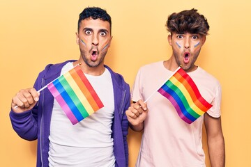 Young gay couple holding rainbow lgbtq flags scared and amazed with open mouth for surprise,...