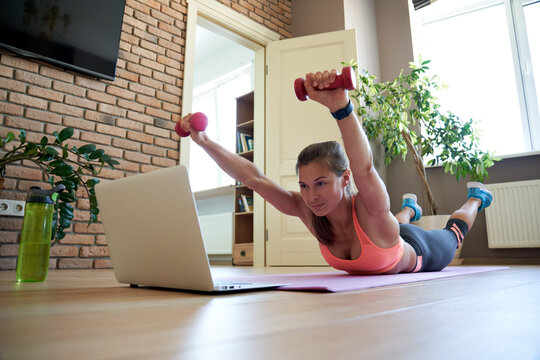Active fit sporty young woman holding dumbbells doing superman fitness exercise training abs and back at home on mat watching online video training tutorial sport live stream workout class on laptop.