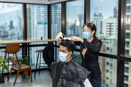 Young good looking male customer takes hair cut in a sky creeper business office while barber puts hygienic face mask and shield on to protect virus infection as a business in new normal.