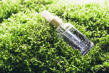 Cosmetic liquid gel products on green moss background. Beauty skin care concept