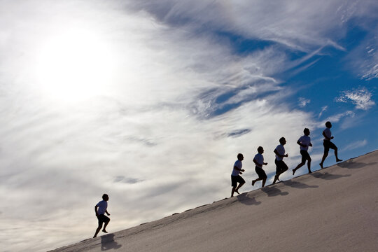 business concept success,competition,people running uphill outdoors su clouds and blue sky with group leading and one lonely runner left behind struggle to keep up