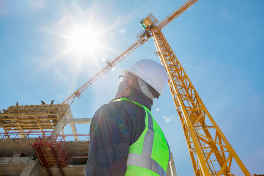 architect or construction worker or civil engineer or foreman with hard hat and safety vest on construction site  with crane and sun flare