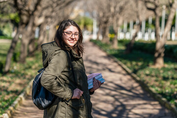Intellectual young girl stays and look to someone in a park with some books in her hands.