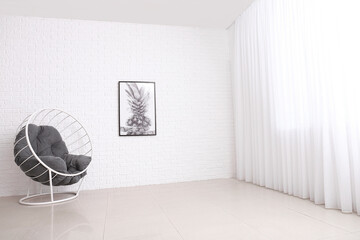 Armchair near white brick wall in room