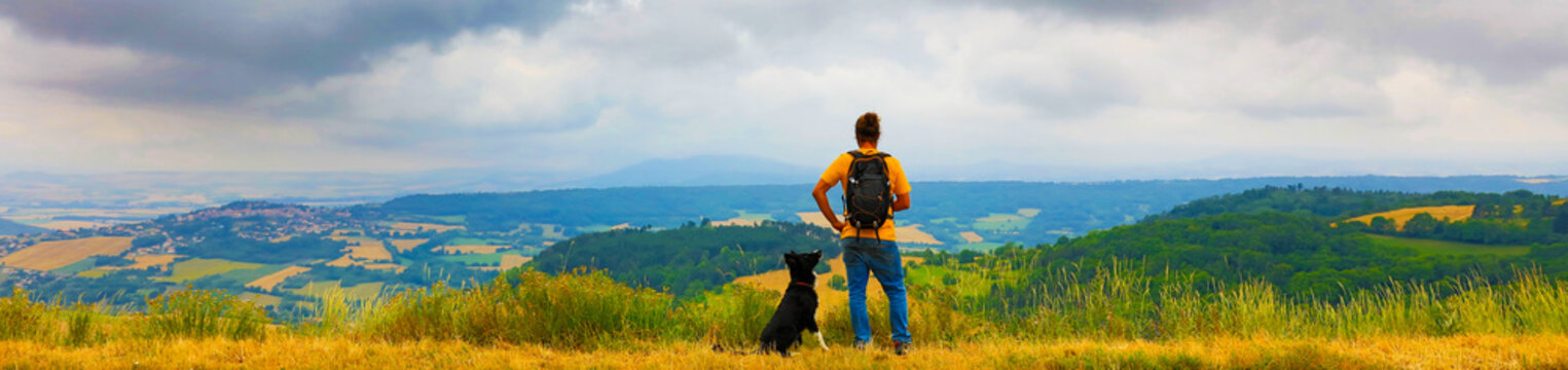 man backpacker with dog looking at landscape view, France- Auvergne
