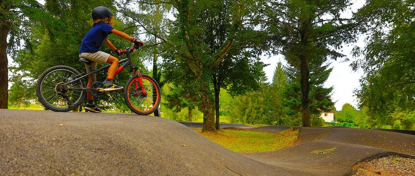 young boy riding on a bike-pumptrack, skatepark-BMX rider on a bike ready to start