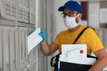 Mailman delivering mail with mail-bag and protective mask and gloves during virus pandemic.