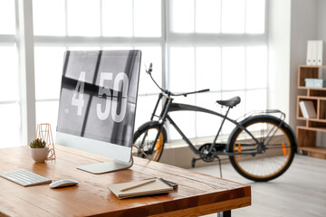 Stylish interior of room with workplace and bicycle