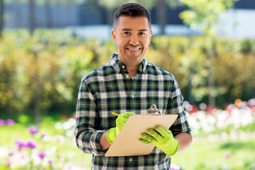 gardening and people concept - middle-aged man writing to clipboard and taking care of flowers at summer garden