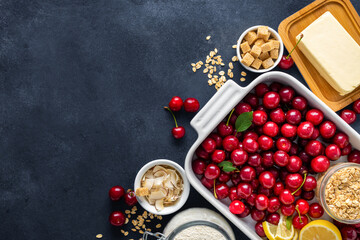 Ingredients for cooking pie with cherries on dark background with copy space top view