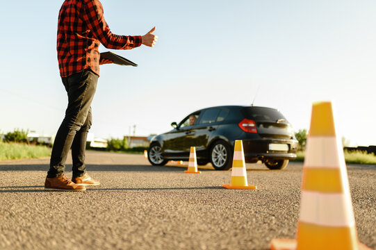 Instructor helps student to drives between cones