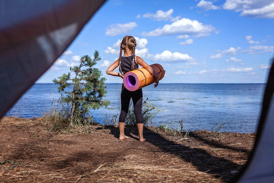 Mental and physical health, safe active lifestyle. Girl doing yoga in campsite on bank of the see