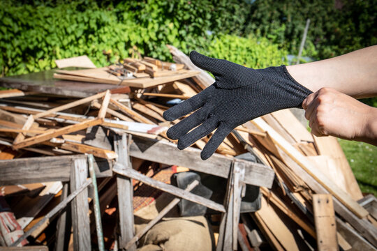 Wooden debris at the yard, boards and plates. Getting ready for work, pulling black gloves on hand. Construction and reconstruction