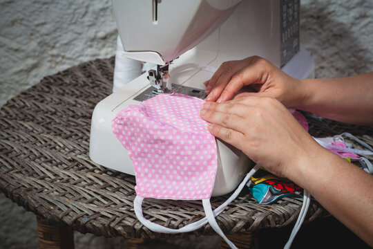 woman seamstress hands sewing with a sewing machine a handmade face mask pink and polka dots