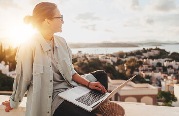 Beautiful curly young girl with glasses working on a laptop with a city view at sunset. Modern technologies, urban lifestyle. Freelance and online education
