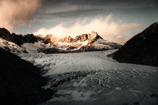 Scenic view of Rohnegletscher glacier valley with mountain in background during sunset