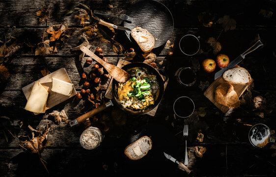Eierpfanne mit Avocado und Mozzarella auf einem Tisch mit Brot und Butter und Kastanien