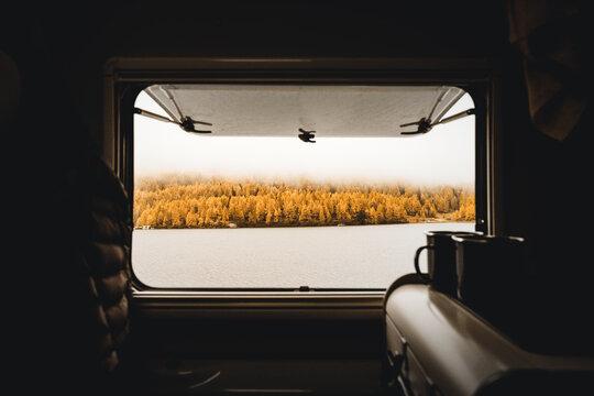 Bilck aus dem Fenster eine Campervans auf den Silvaplanersee bei St.-Moritz in den schweizer Alpen mit bewölktem Himmel und Lerchen im Hintergund in herbstlichen Farben.