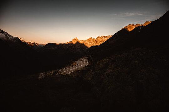 Pass Strasse zum Sustenpass in den Schweizer Alpen bei Sonnenuntergang. Die Gipfel im Hintergrund erleuchten im Abendrot.