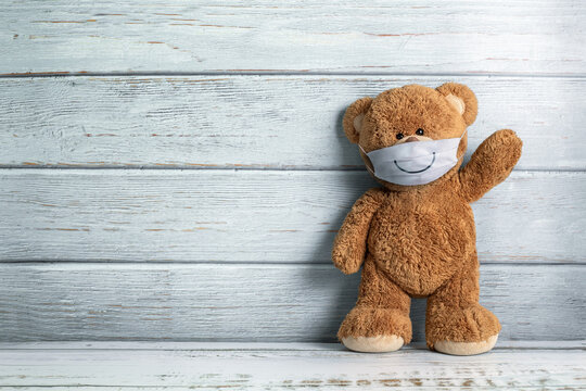 Cute teddy bear smiling behind the mask have a happy face for social distancing concept. with copy space.