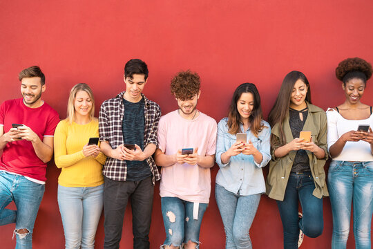 Group young friends using mobile smartphone outdoor - Millennial generation having fun with new trends social media apps - Youth technology people addicted - Red background