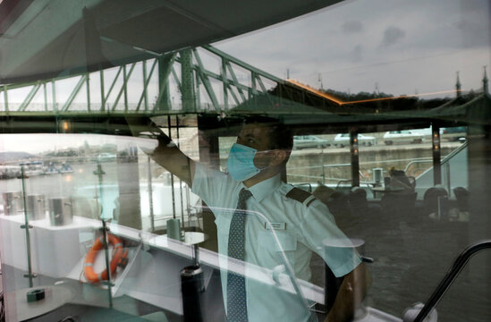 A crew member clean the window at onboard the NickoVision river cruise boat following the coronavirus disease (COVID-19) outbreak in Budapest