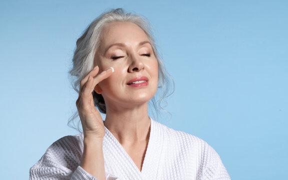Senior woman with eyes closed putting cosmetic moisturizing rejuvenating cream on face