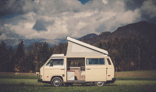 White, medium size vintage hippie caravan without logos in a nice spot landscape with mountains and trees on the background. Adventure, outdoor recreation, adventures in nature, vacation.