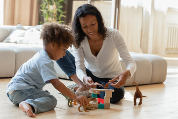 Playful young african American mother sit on floor in living room play toys with little son, loving...