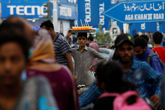 A man carries a tray of orange juice glasses while selling them amidst the rush of people outside an electronics market as the outbreak of the coronavirus disease (COVID-19) continues, in Karachi