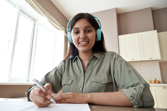 Smiling indian teen girl school student wear headphones look at webcam distance learn or teach online. Zoom lesson video call remote class, online education concept. Headshot portrait. Webcamera view.