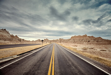 Poster Montagne Scenic road in Badlands National Park, color toning applied, travel concept, USA.