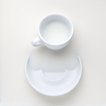white coffee cup and saucer in milk