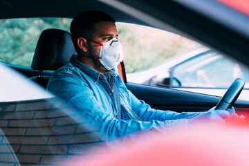 Man with mask and gloves driving a car.