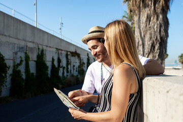 Happy tourist couple checking a city map outdoors in a sunny day