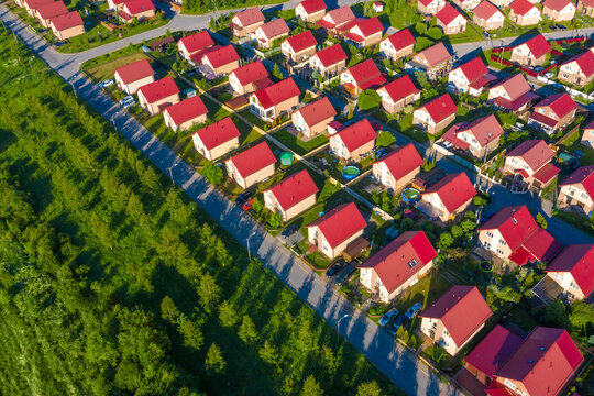 Suburb top view. Suburbia. Two-story houses in suburbs. Concept - low-rise buildings. Houses with red roofs on a summer day. Cottage village view from a quadcopter. Suburbia top view. Suburban homes