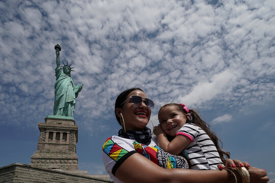 People pose for a photo at the Statue of Liberty as New York enters Phase 4 of reopening following the outbreak of the coronavirus disease (COVID-19) in New York City