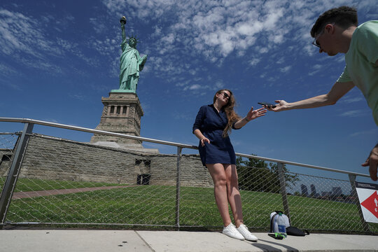 A person retrieves her mobile phone after posing for a photo at the Statue of Liberty as New York enters Phase 4 of reopening following the outbreak of the coronavirus disease (COVID-19) in New York City