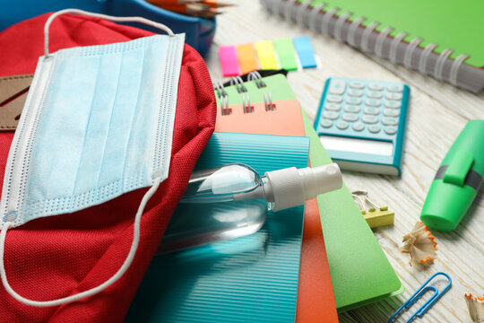 School supplies with medical mask and sanitizer on wooden background, close up