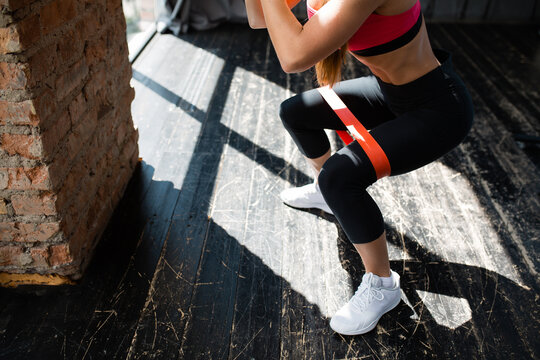 Close-up shot of woman squatting leg with elastic thigh expander for pumping muscles of thighs and legs in a loft in front of a panoramic window